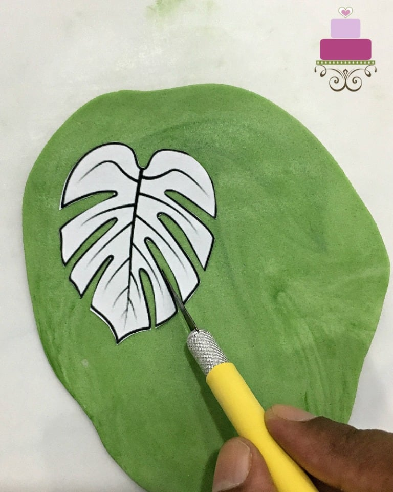 Cutting a fondant leave using a paper template and sugarcraft knife