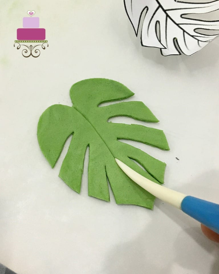 Shaping a green fondant leaf