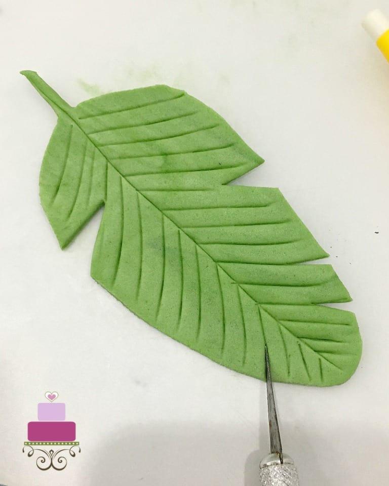 A green fondant palm leaf