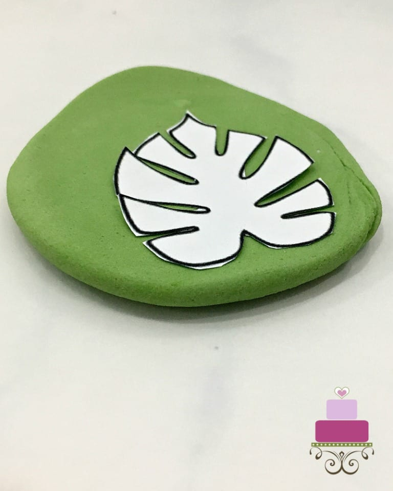 Leaf paper template on green rolled fondant