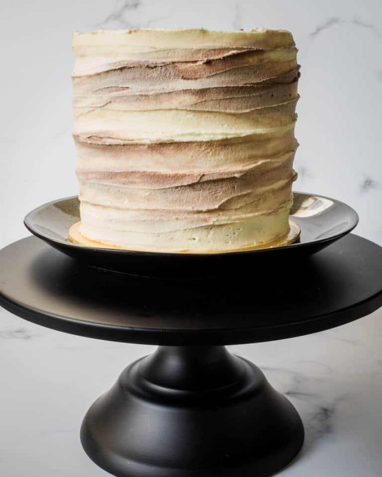 A round cake with marbled buttercream icing, on a black cake stand.