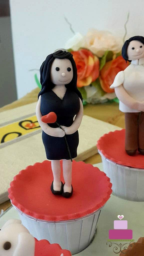 A cupcake with a lady figurine topper