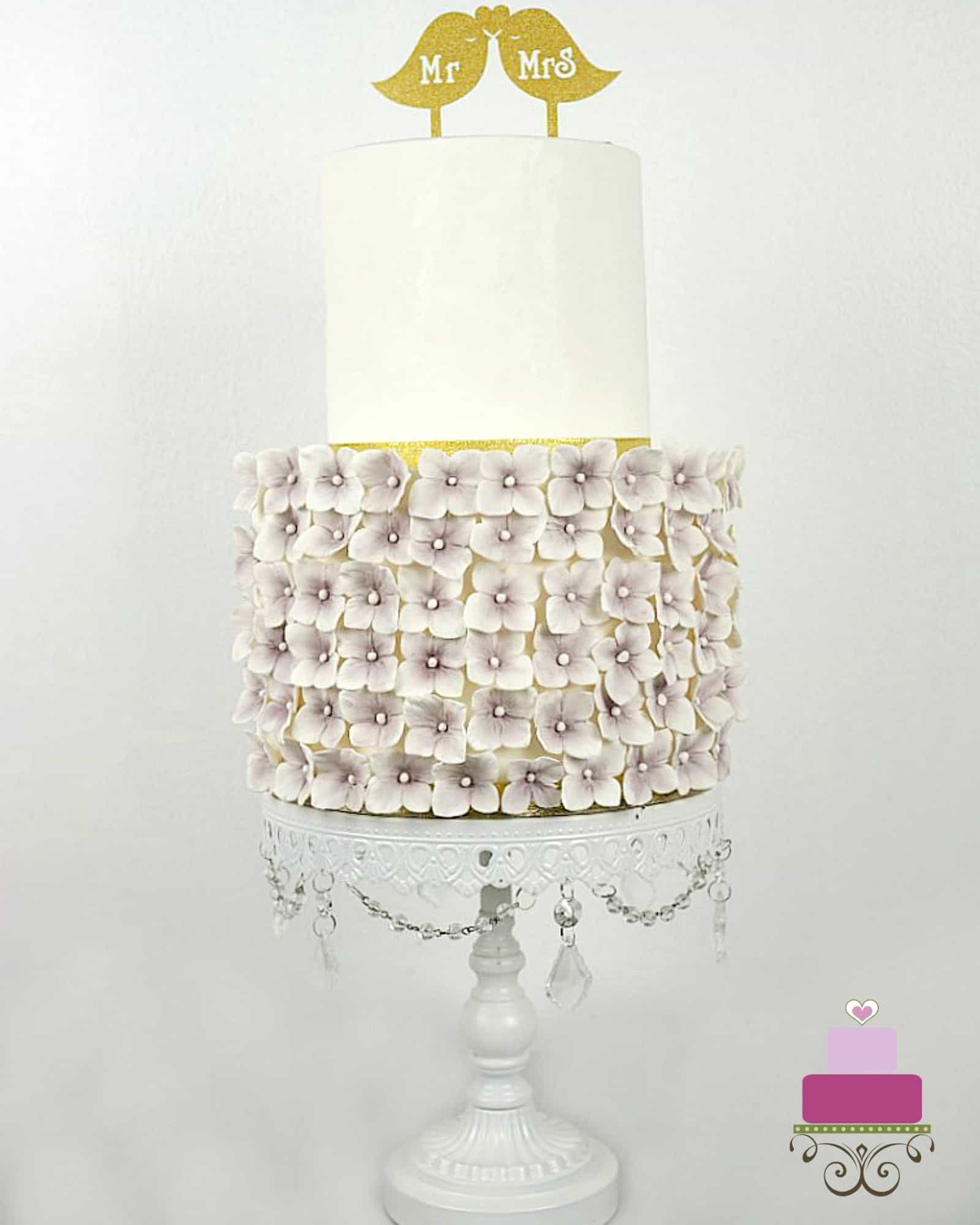 A 2 tier cake with the second tier covered in purple hydrangeas. Cake topper is a gold Mr & Mrs Birds paper pick.