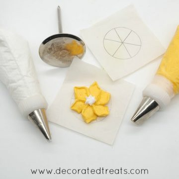 2 piping bags filled with white and yellow royal icing, with a flower nail and a pipe yellow flower in between