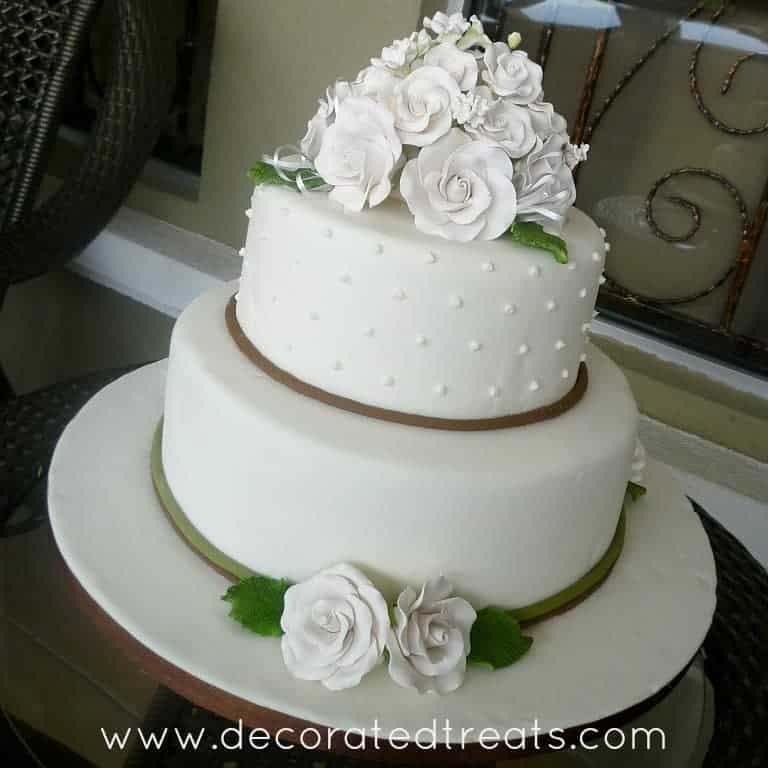 A 2 tier cake in white fondant and matching white roses