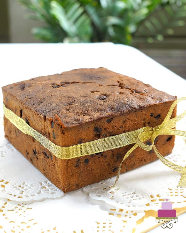 A square light fruit cake tied with a golden ribbon