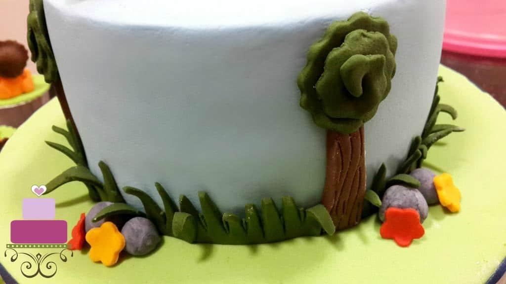 A fondant tree and fondant grass deco on a blue cake