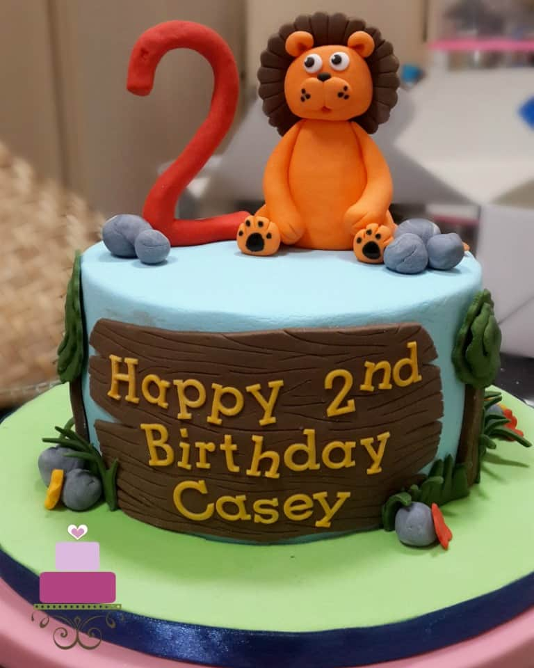 A round cake with a lion and number 2 cake topper.