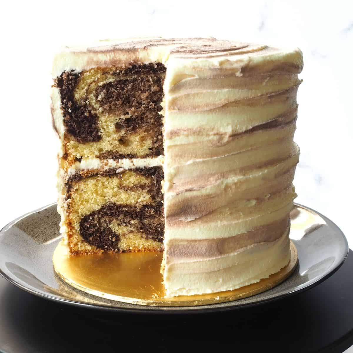 A round marble cake covered in marbled buttercream. A slice of the cake is cut out