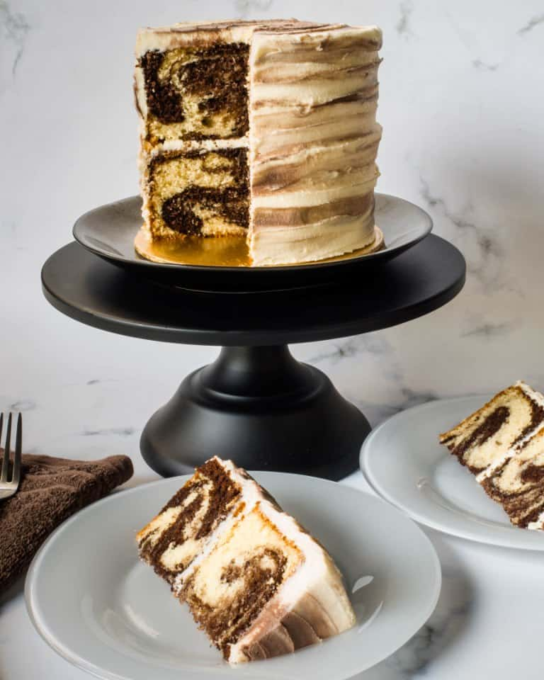 A round marble cake covered in marbled buttercream. 2 slice of the cake is cut out onto white plates