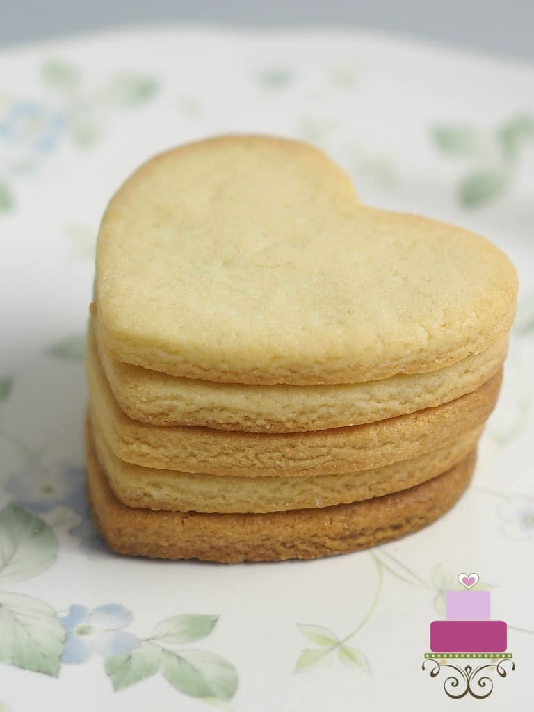 A stack of 5 heart shaped cut out cookies on a green floral plate