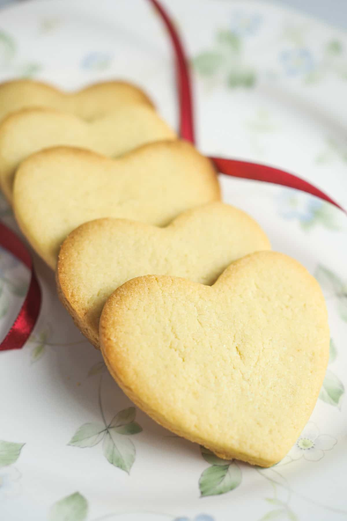 A row of overlapping heart shaped cookies on a floral plate
