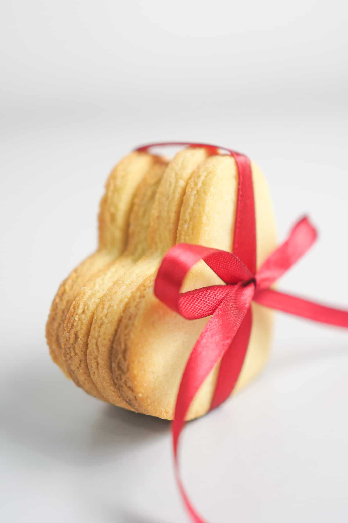 A stack of 4 heart shaped, no spread sugar cookies tied in red ribbon