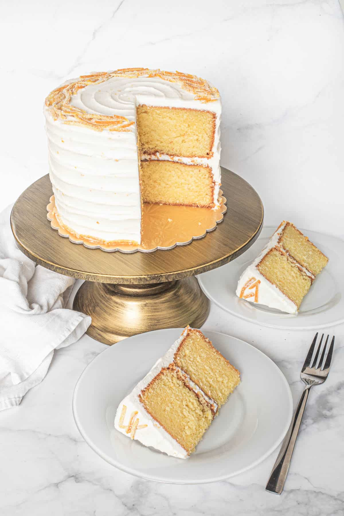 A round cake decorated with candied orange peels. 2 slices are cut out onto white plates