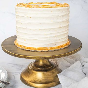 A round cake covered in white buttercream on a gold cake stand