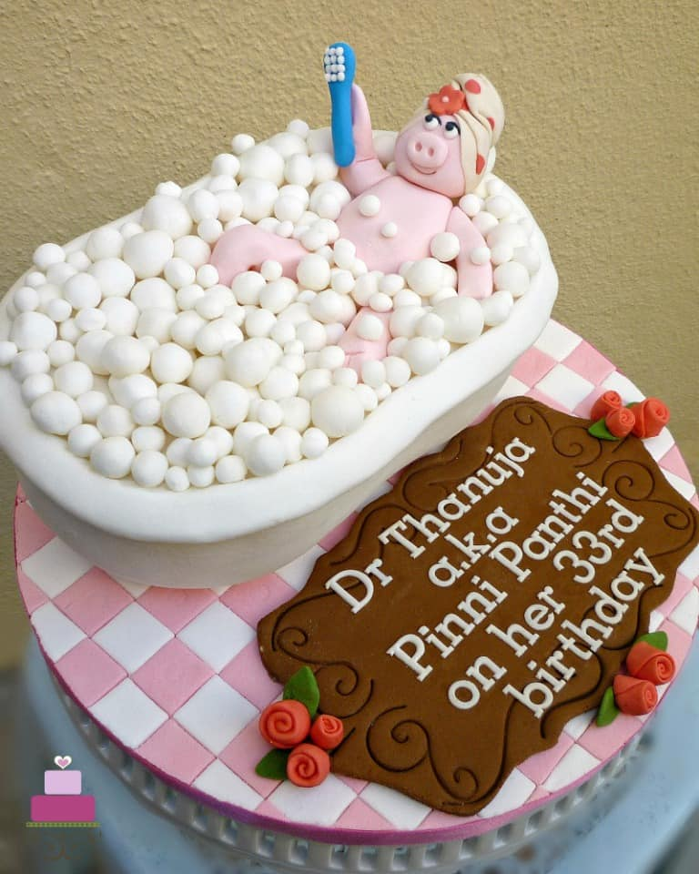 A bath tub shaped cake with a 3D fondant pig holding a brush in it. Cake is topped with fondant bubbles and placed on a pink and white checked cake board with a large brown birthday wish plaque