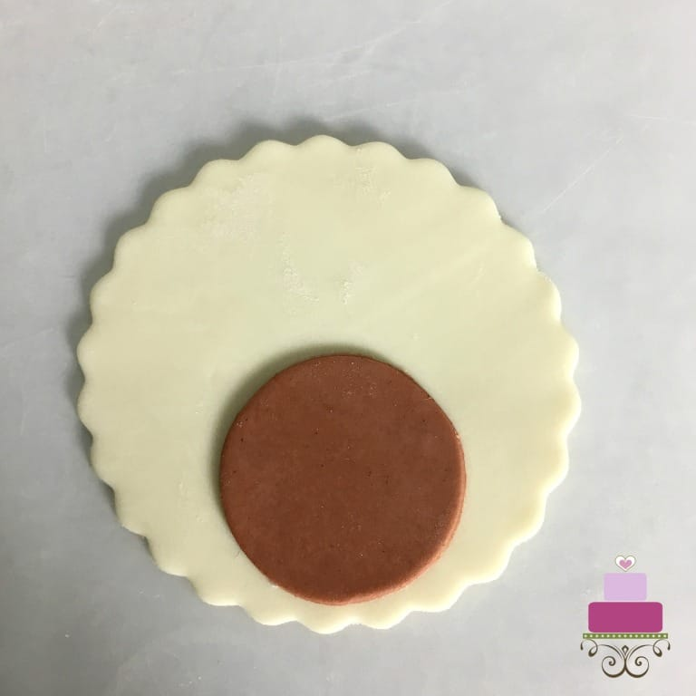 A smaller piece of brown circle fondant cut out on a large piece of white circle fondant