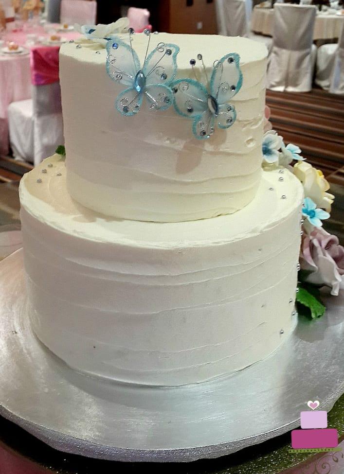 2 blue wired butterflies on a buttercream wedding cake
