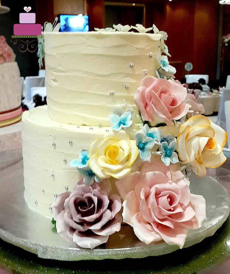 A two tier wedding cake with rustic buttercream deco, pink, purple and yellow roses and blue hydrangeas