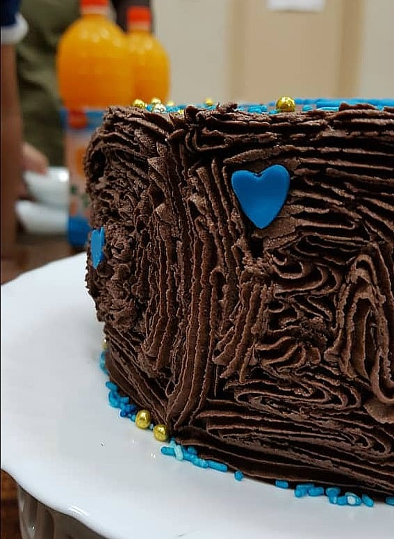 A round chocolate cake covered in chocolate icing and decorated with blue hearts and sprinkles.
