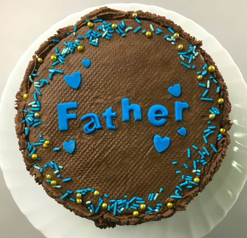 A round cake covered in piped chocolate icing, with blue alphabets spelling 'Father'. Cake is decorated with blue hearts and sprinkles in blue and gold.