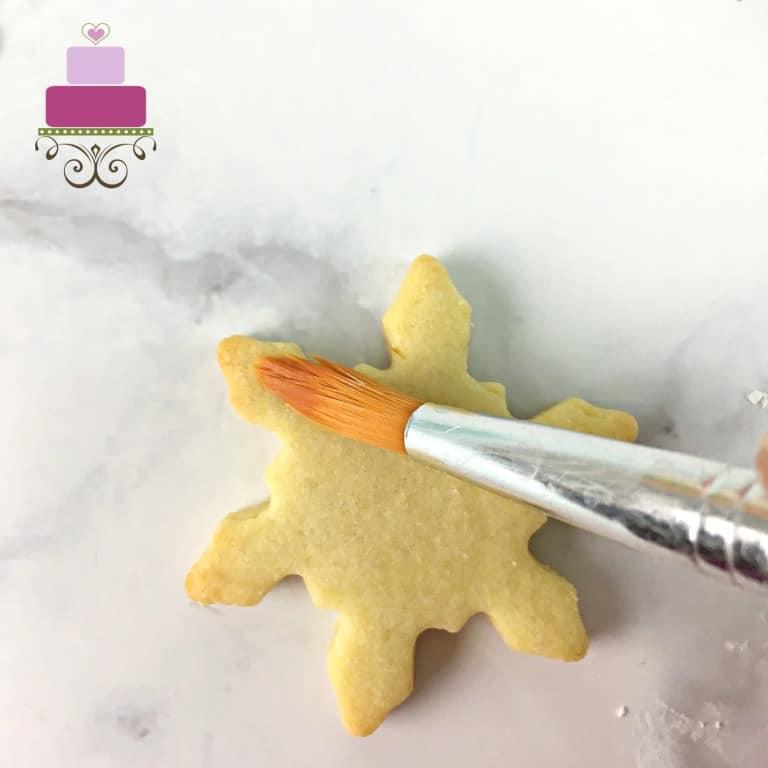Brushing a snowflake sugar cookie