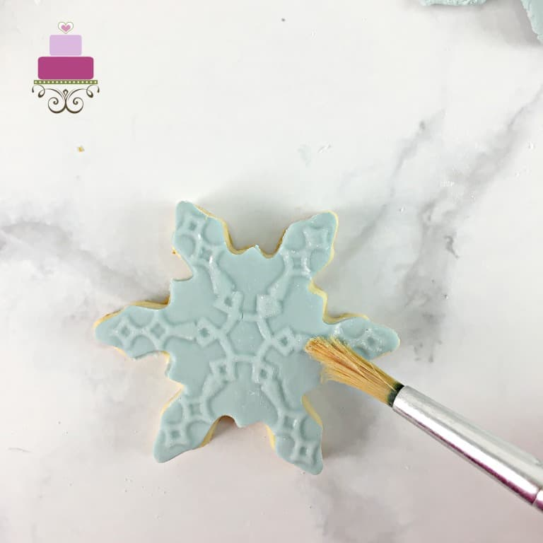 Brushing a blue snowflake sugar cookie