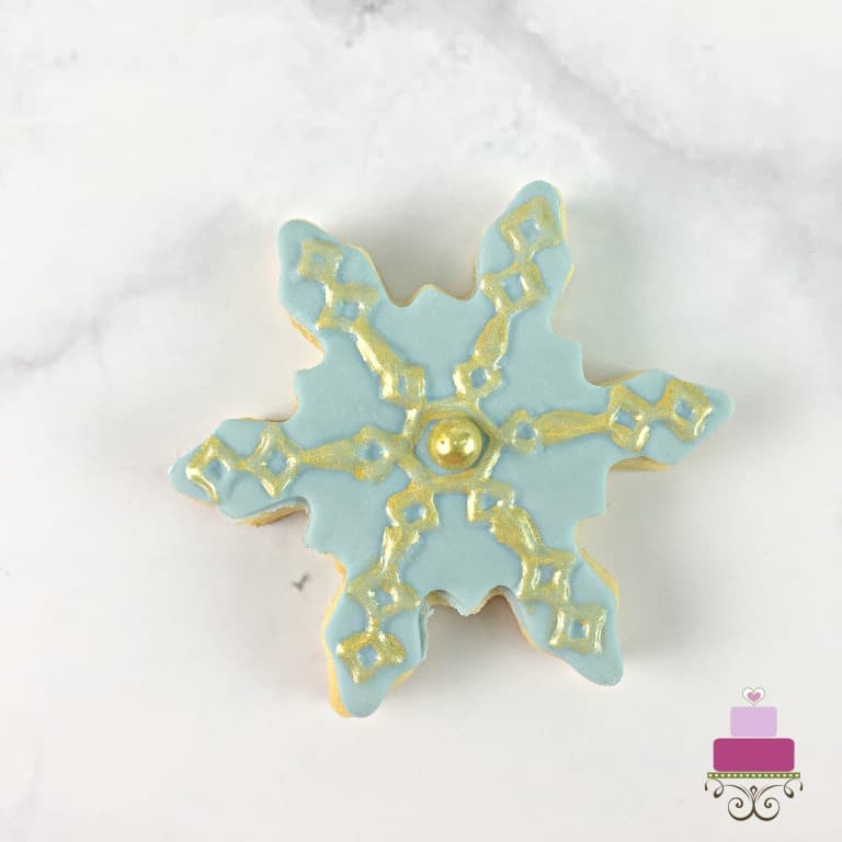 Blue snowflake sugar cookie painted in gold