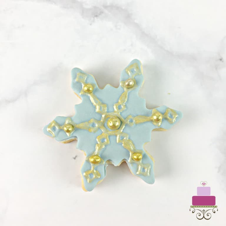 Blue snowflake sugar cookie painted in gold and decorated with gold dragees