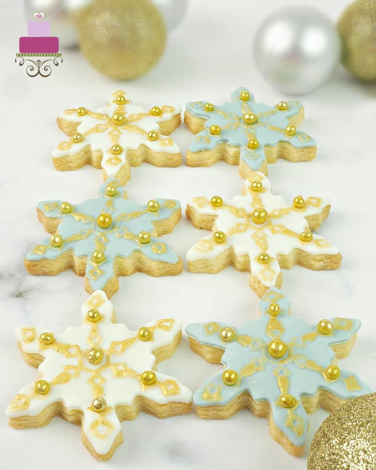 Sugar cookies in the shape of snowflakes decorated in blue, white and gold