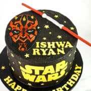 A round cake decorated with Darth Maul face image and lightsaber topper