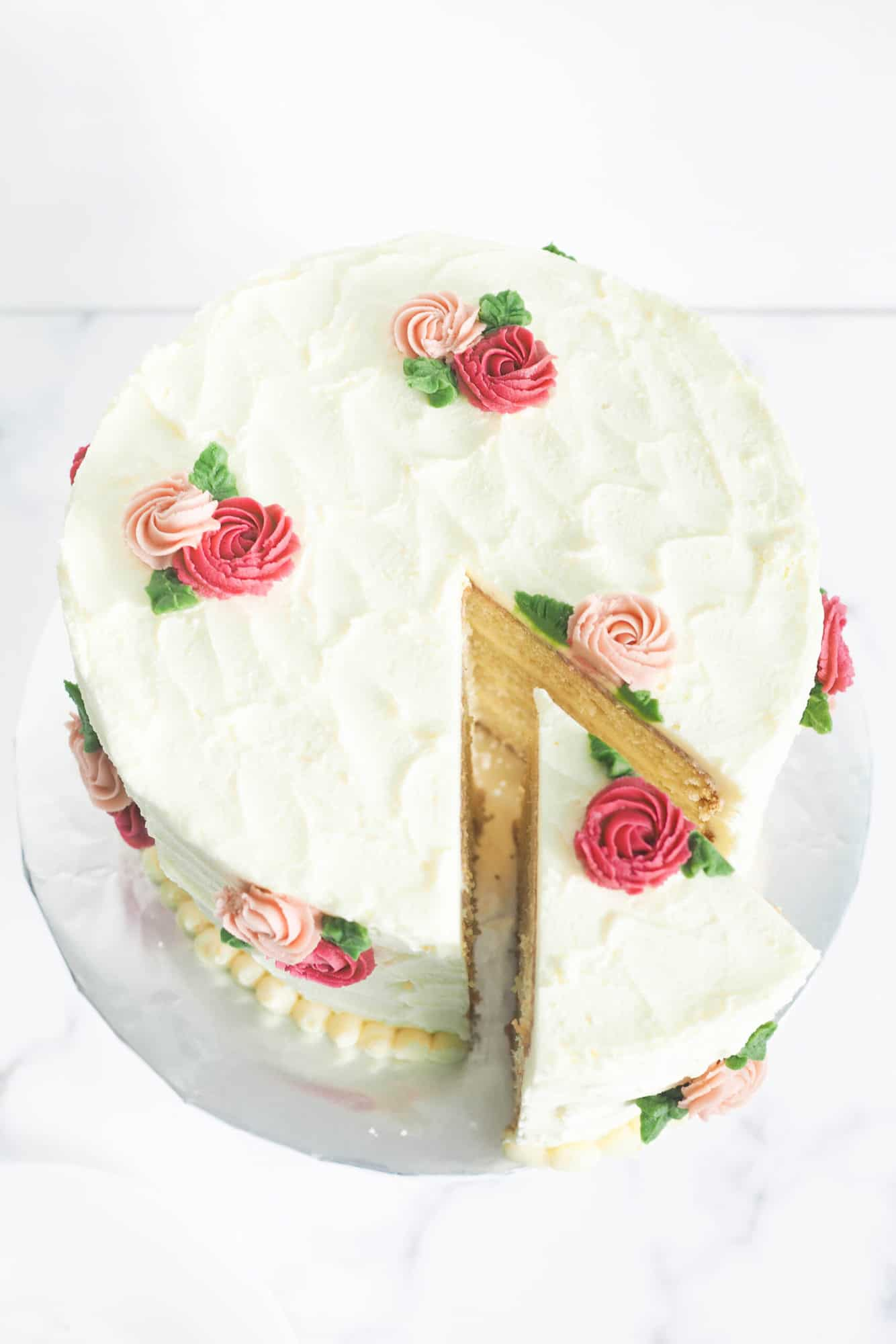 A round cake covered in white buttercream with pink and maroon rosettes and green leaves. A slice of the cake is cut out.