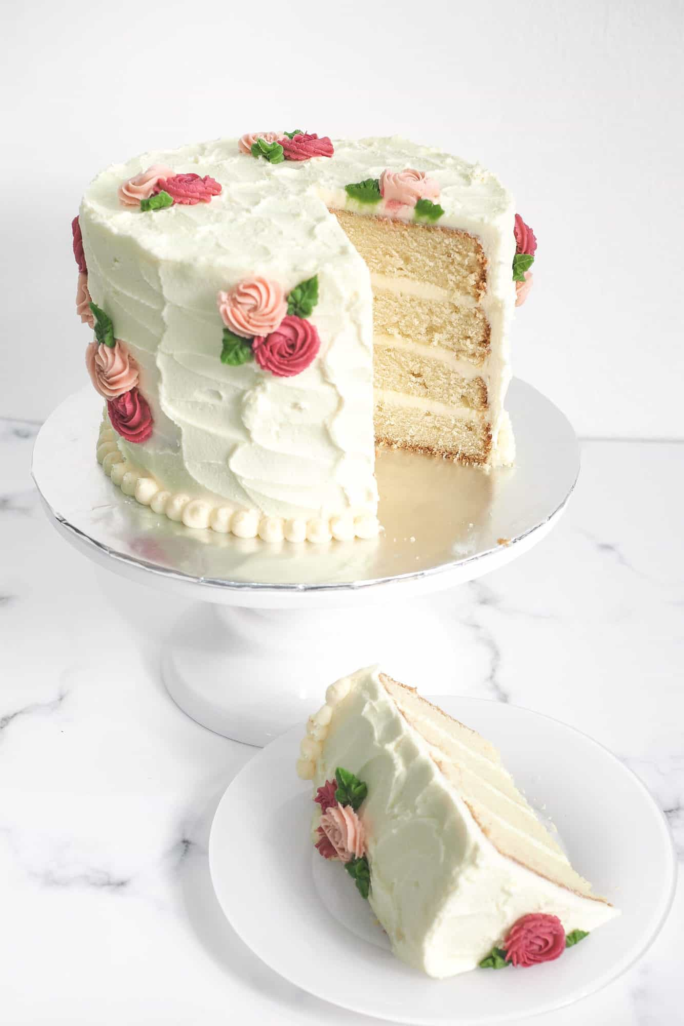A round cake covered in white buttercream with pink and maroon rosettes and green leaves. A slice of the cake is cut out onto a white plate.