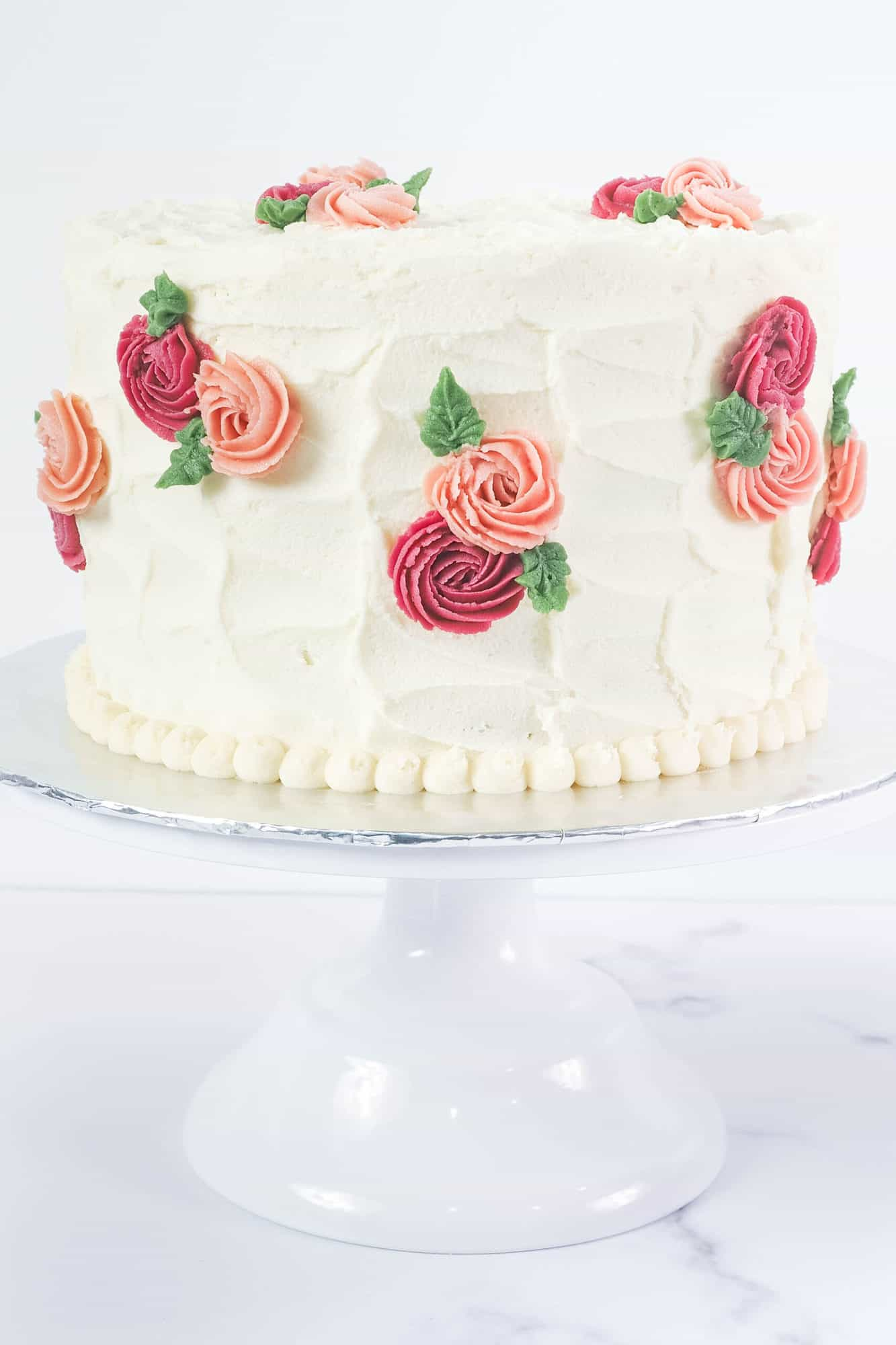 A round cake covered in white buttercream with pink and maroon rosettes and green leaves. Cake is on a white cake stand