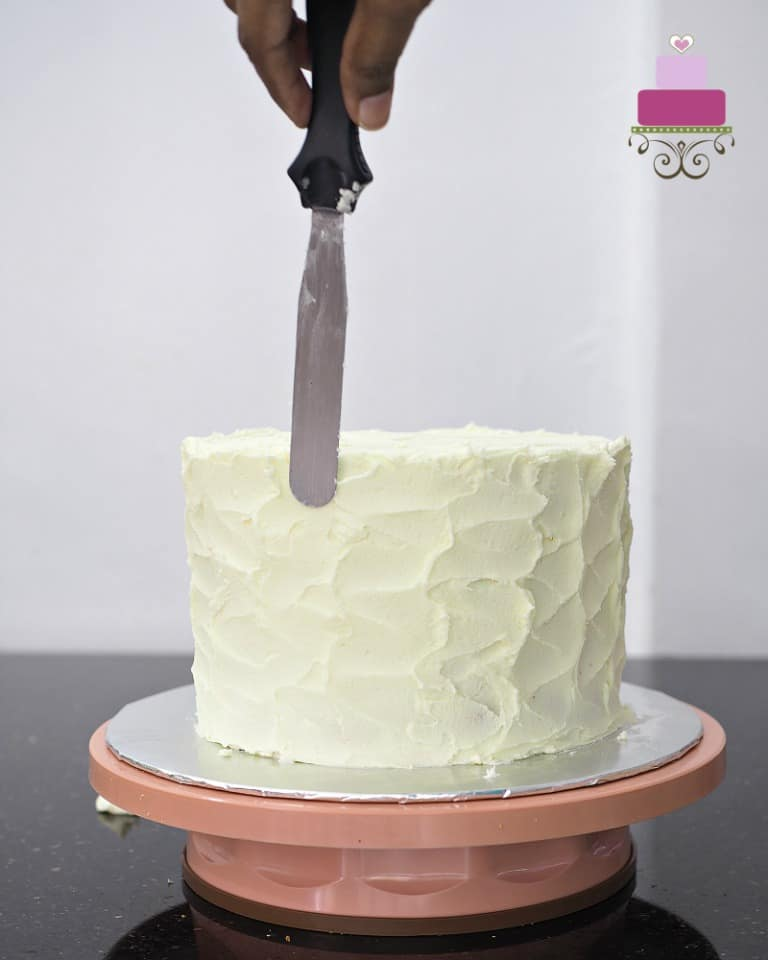 Using a palette knife to rough ice a round cake with buttercream