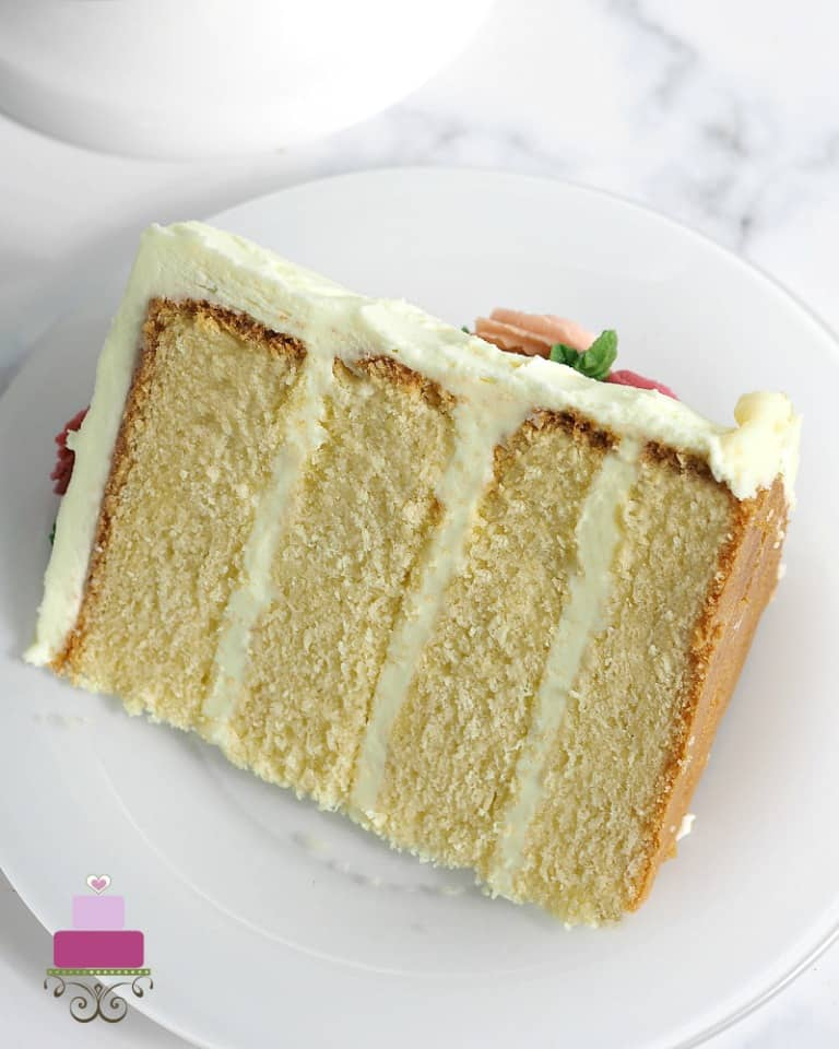 A slice of four layer cake in white frosting on a white plate