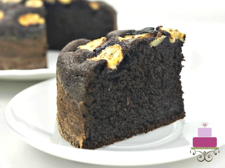 A slice of chocolate cake with banana slices topping on a white plate