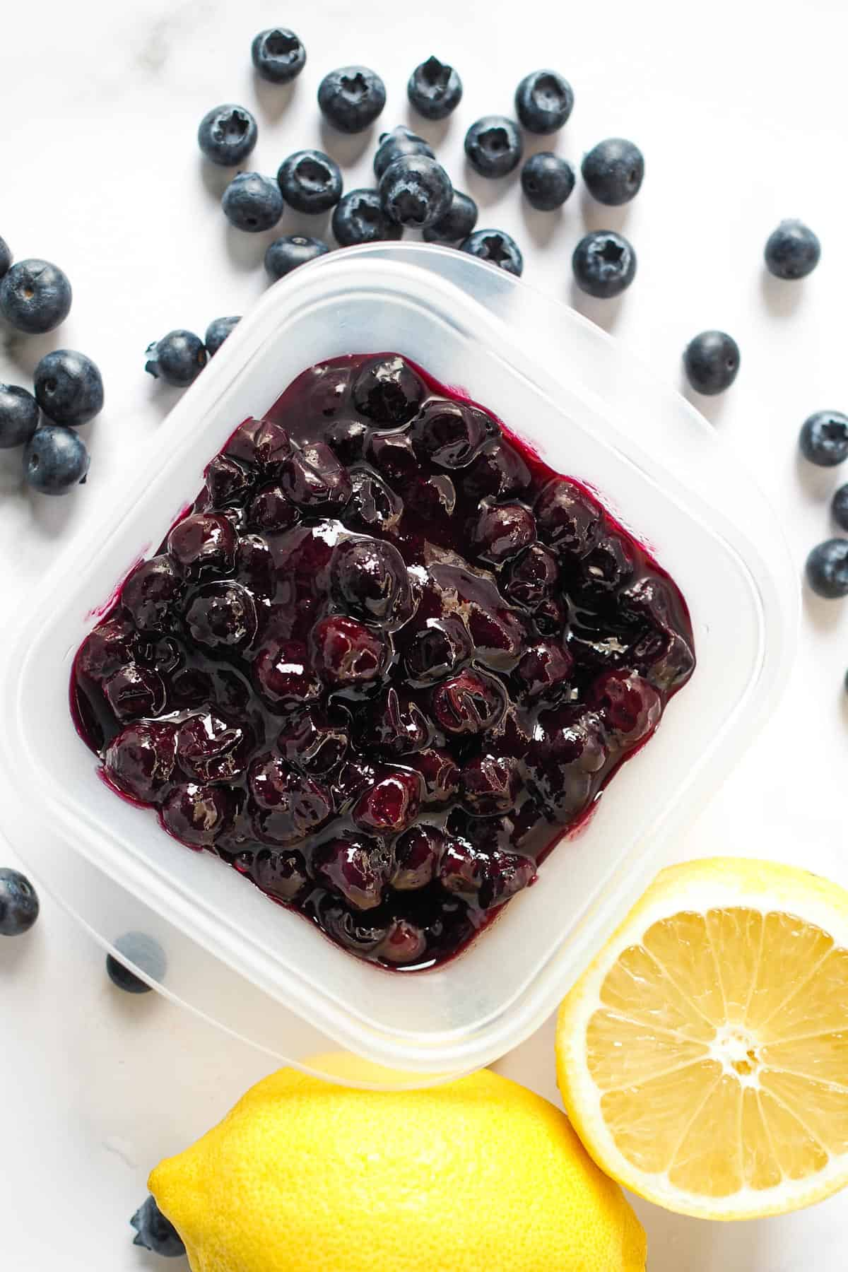 Blueberry pie filling in a square container, with lemon and fresh blueberries on the side