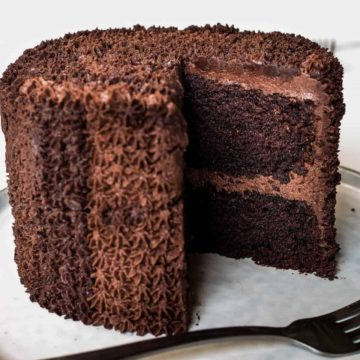 A round chocolate cake covered in chocolate icing and a slice cut out.