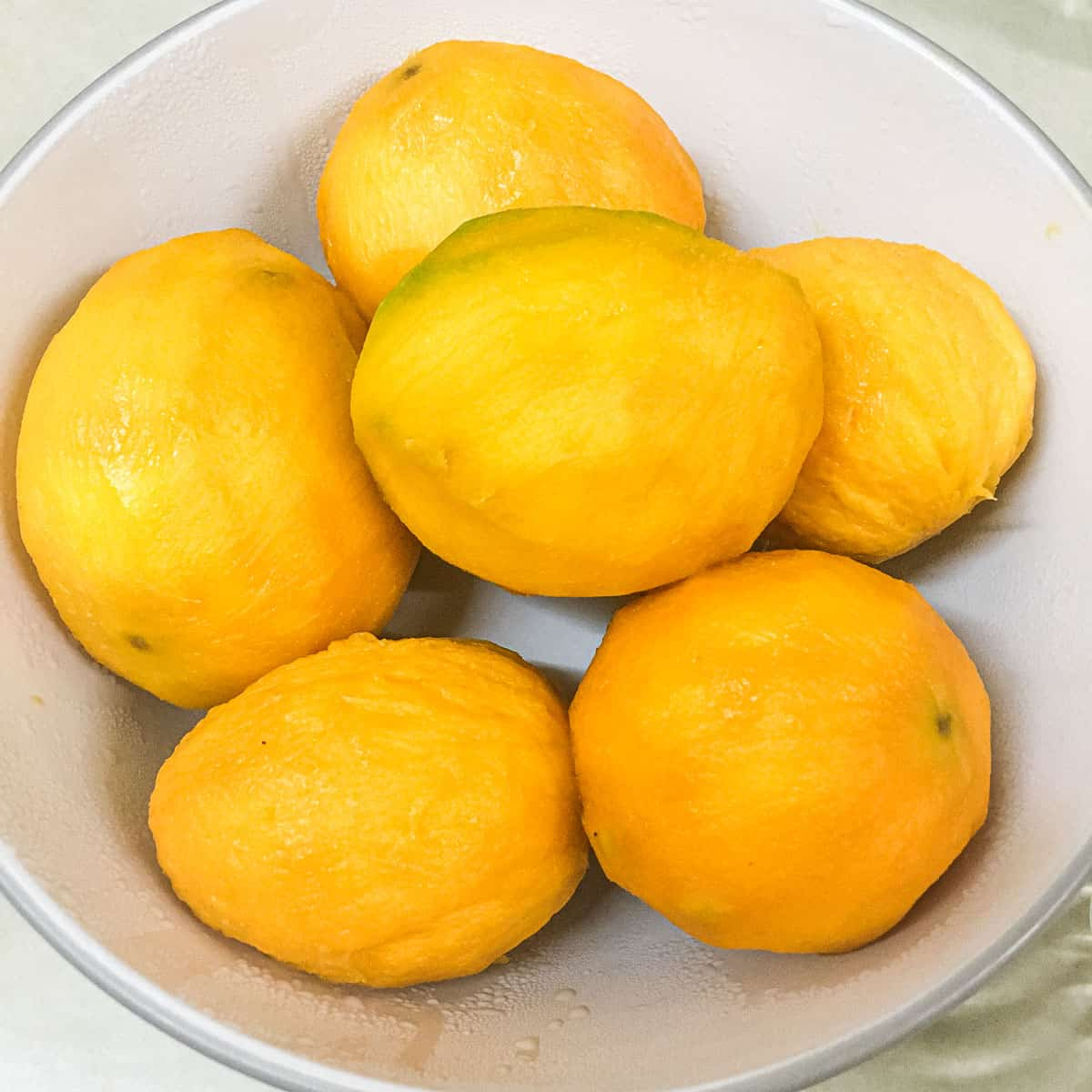 A bowl of ripe and peeled mangoes
