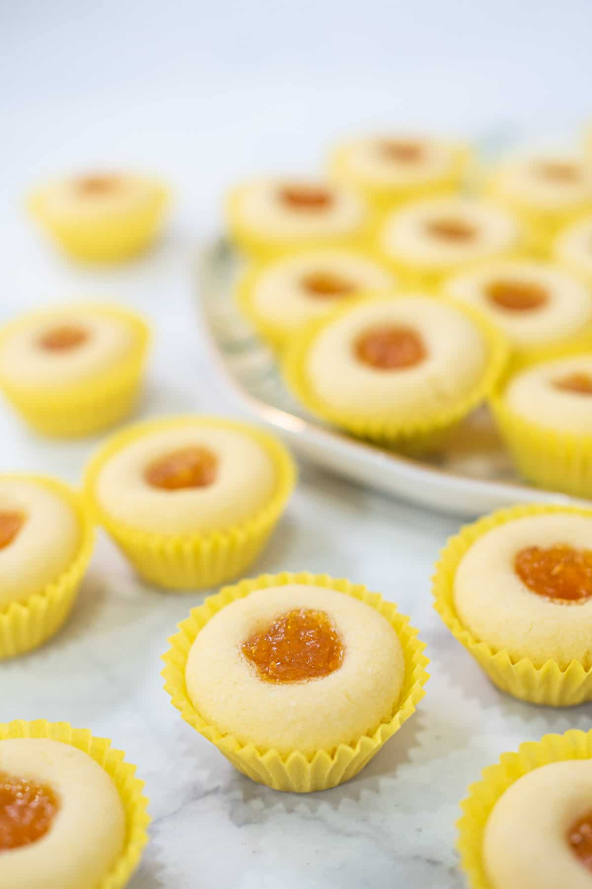 Jam filled cookies in yellow casings, against a marble background