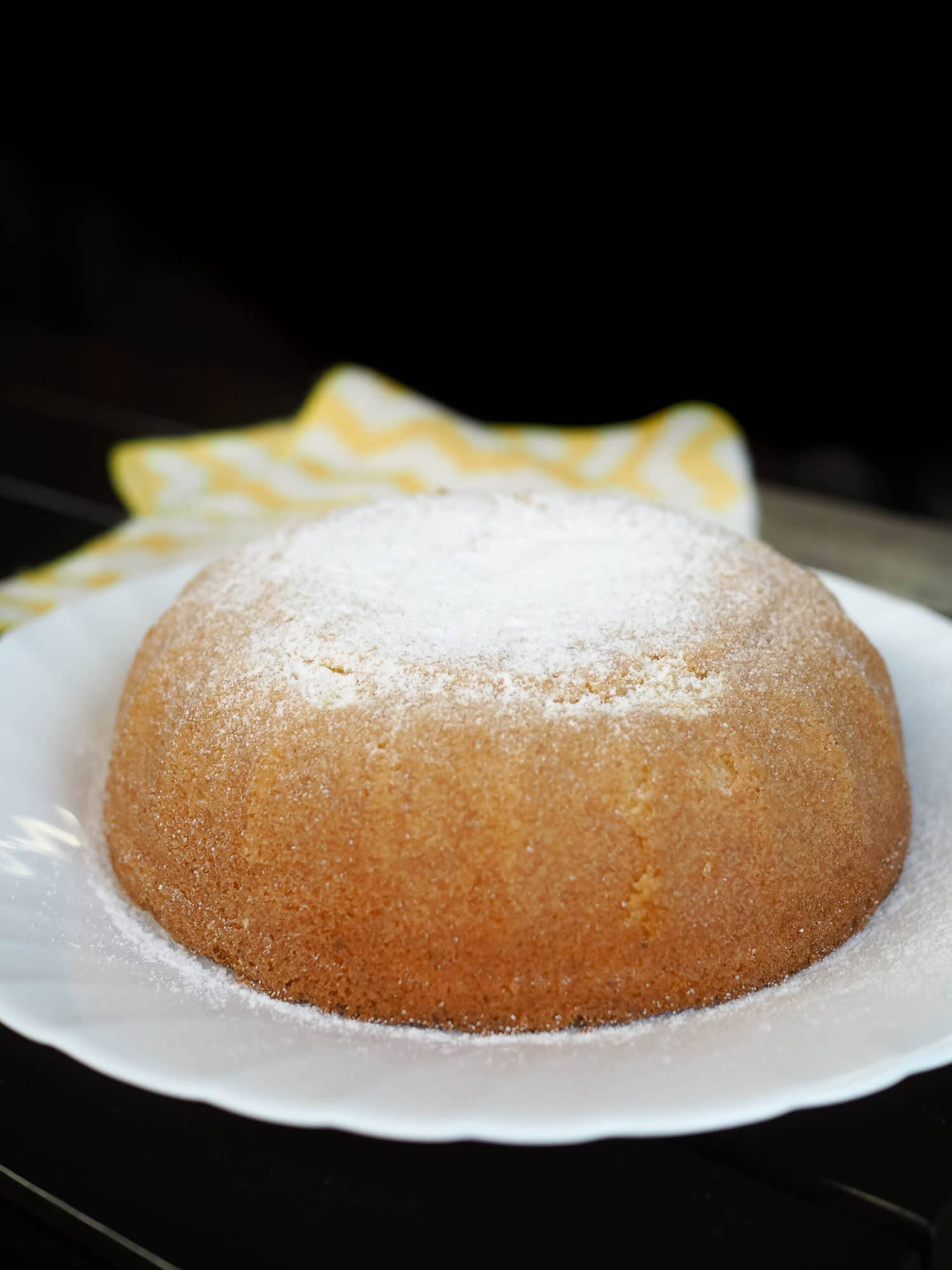 A bowl shaped cake with powdered sugar topping