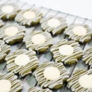 Flower shaped matcha shortbread cookies decorated with white chocolate button centers and glaze icing drizzle on a wire rack.