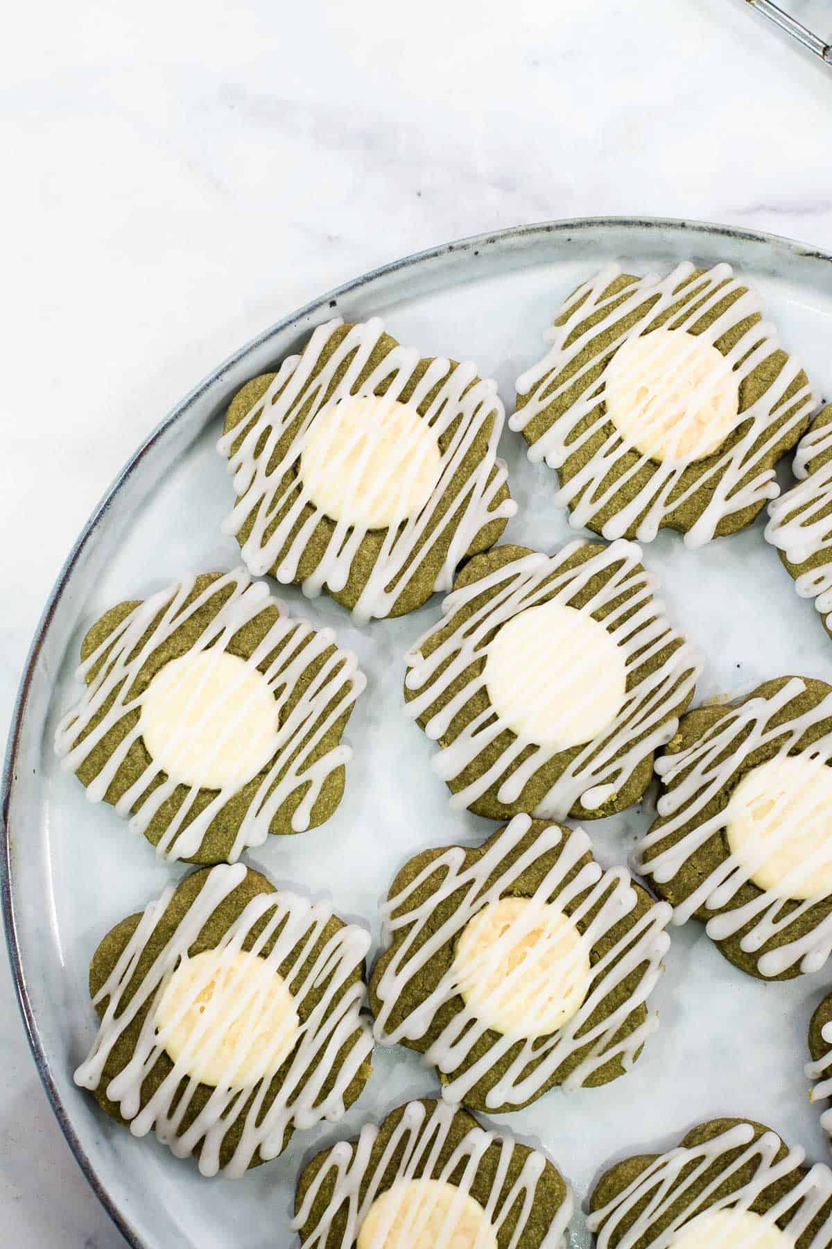 Close up view of a plate filled with green flower shaped cookies with white centers and icing drizzle