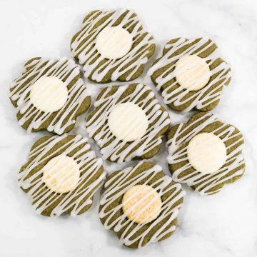 Green cookies decorated with white chocolate button centers and glaze icing drizzle, arranged in a circle