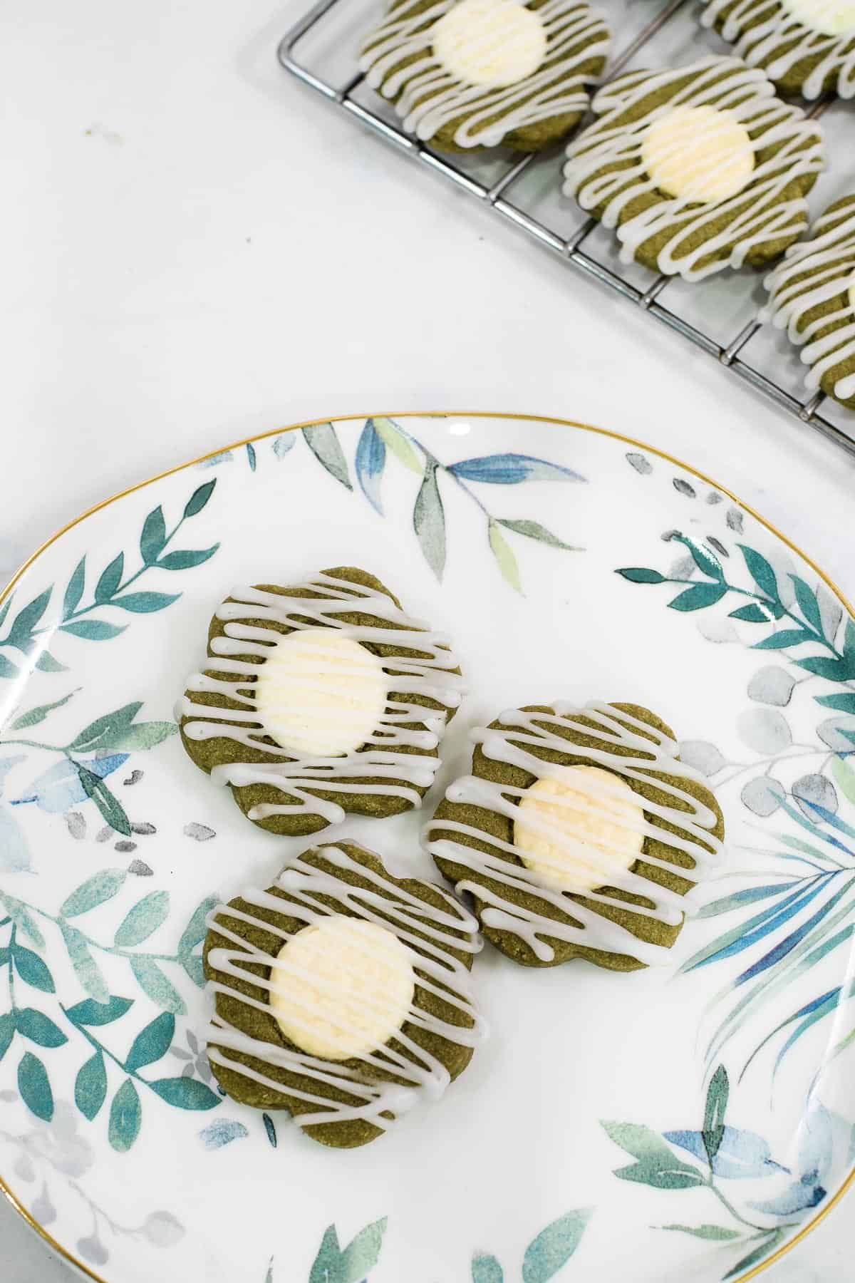 3 flower shaped green cookies with white centers and glaze icing drizzle on a white plate with leaves motif.