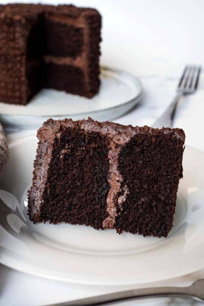 A slice of a chocolate cake covered in chocolate icing, cut out onto a white plate