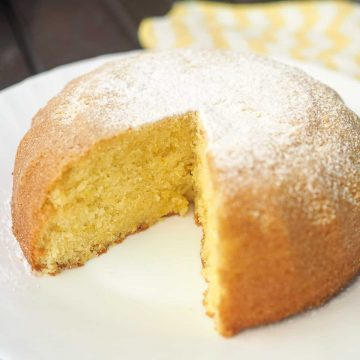 A bowl shaped cake with powdered sugar topping with a slice cut out.