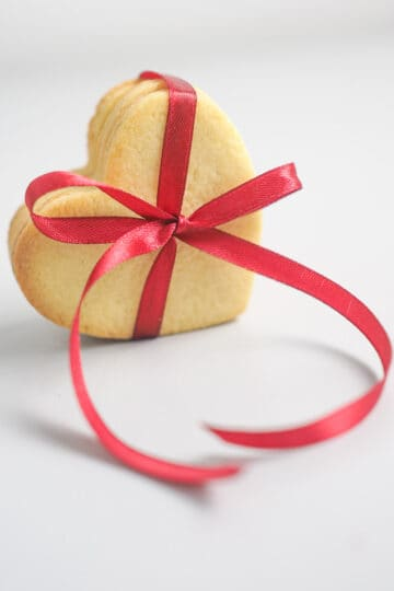 A group of heart shaped cookies tied together with a red ribbon