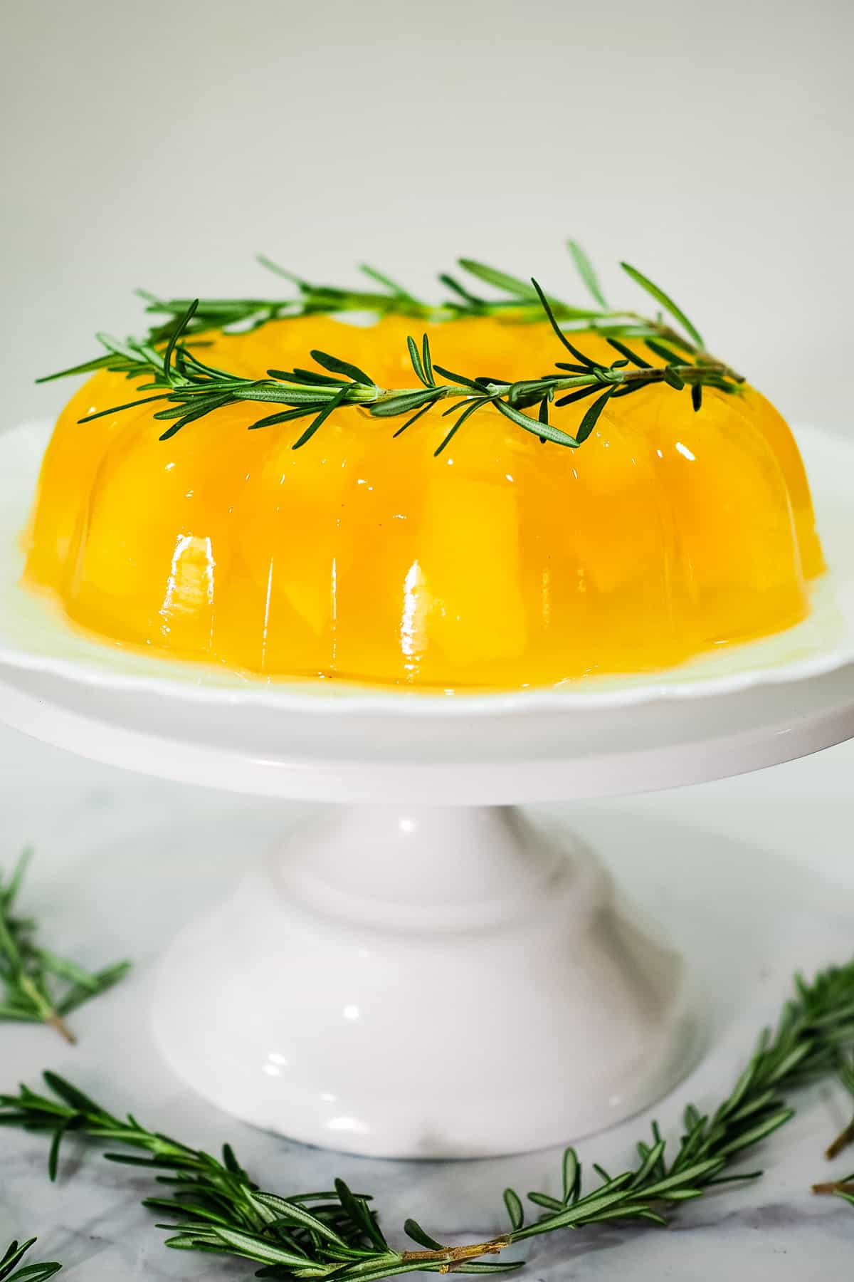 A yellow jelly in a bundt shape with rosemary leaves garnish